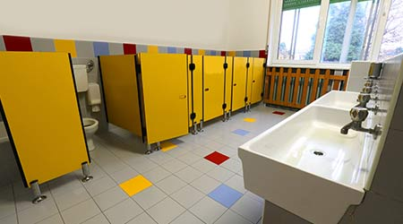 inside a wide bathroom with yellow doors of a kidergarten