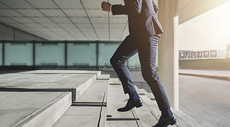 Businessman running up stairs in a suit