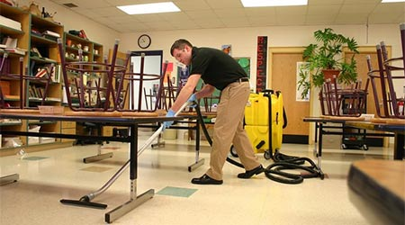 man cleaning a floor in a school