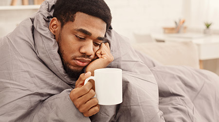 man with flu wrapped in warm blanket, holding cup with tea