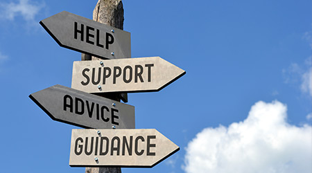 wooden signpost with arrows pointing to help, support, advice and guidance