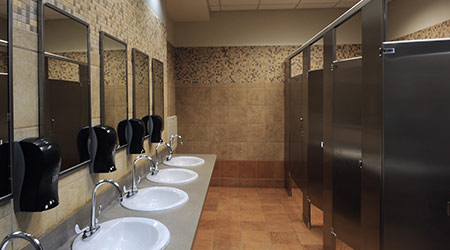 A public restroom with sinks and stalls