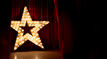 golden star with light bulbs on red velvet curtain on stage