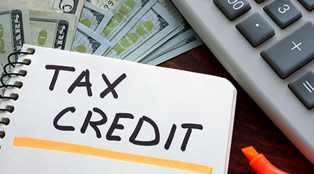 Tax credit written on a piece of paper next to a bunch of money and a calculator