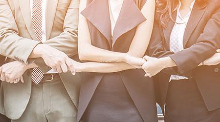 An executive team holding hands