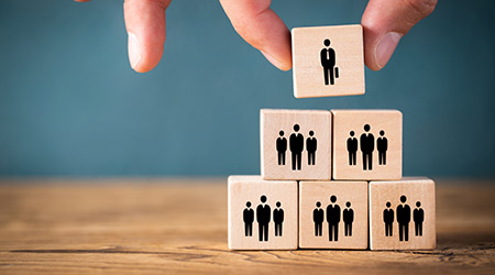 Business and team structure symbolized with stacked cubes, the top of which is being knocked off