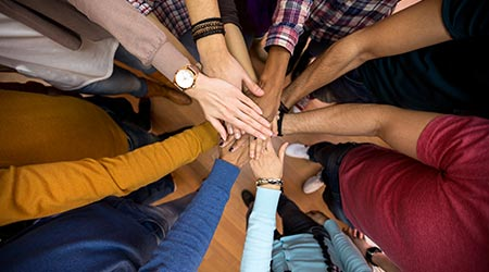 A bunch of people of various races and creeds joining hands in a circle