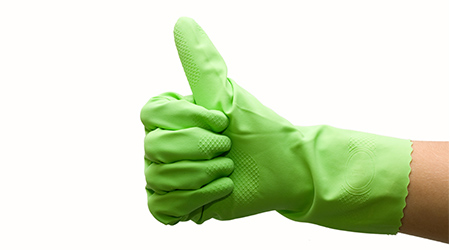 A hand inside a green rubber gloves giving a thumbs up
