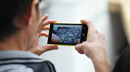 A passerby uses a smartphone to capture an anti-government rally on Jun 30, 2013 in Bangkok, Thailand.
