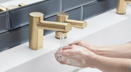 Gold-colored touchless restroom sink fixture