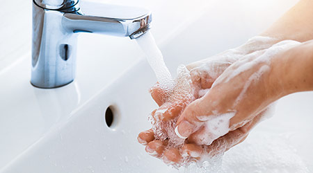 Woman washes her hands in the sink with soap