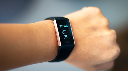 Woman monitoring her heart beat with a fitbit charge 3 activity tracker wearable device on her wrist also known as fitness tracker