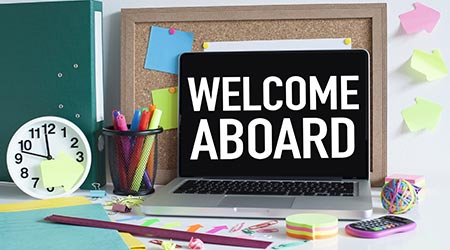 "a blackboard with white text on a work desk that reads ""welcome aboard"""