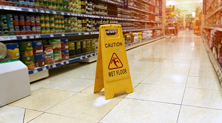 Wet floor is in the supermarket against the background of blurry products standing on the shelves