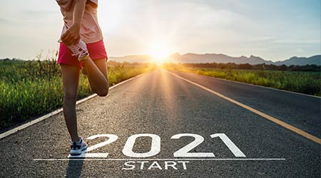 New year 2021 or start straight concept.word 2021 written on the asphalt road and athlete woman runner stretching leg preparing for new year at sunset. Concept of challenge or career path and change.