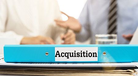 Acquisition documents folder on desk with business people meeting.