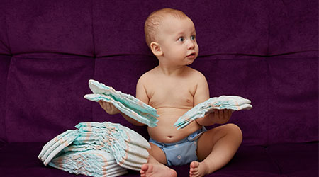 Little boy with stack of diapers or nappies on purple sofa background