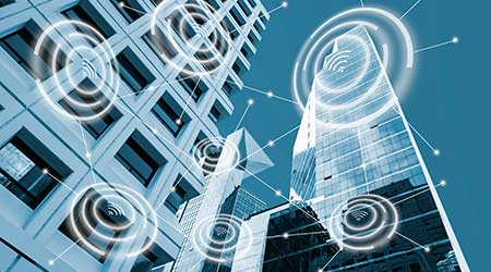 Digital alarm icon and low angle view modern office buildings in blue tone with network connection concept, smart city and wireless communication network, IOT internet of things