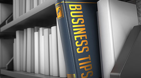 Business Tips - Grey Book on the Black Bookshelf between white ones.