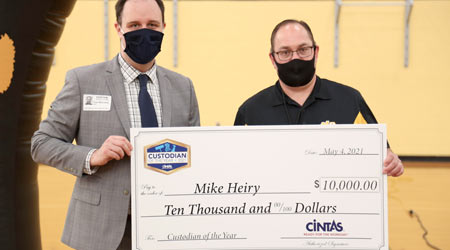 Man in a pandemic mask being awarded check by another man in a covid mask