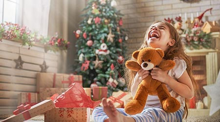 A little girl smiling big after receiving a teddy bear as a gift