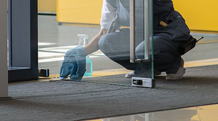 A female janitor cleaning a glass door