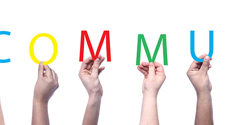 """A bunch of hands holding up colored letters that spell out """"community"""""""