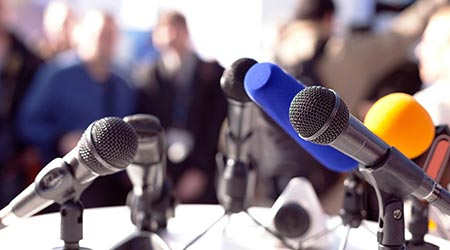 a bunch of microphones at a news conference