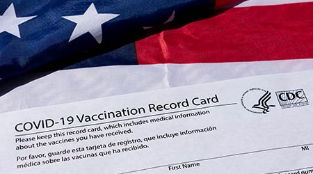 Covid-19 vaccination record card issued by CDC, United States Centers for Disease Control and Prevention, on the flag of the United States of America - San Jose, California, USA - 2021