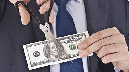 Businessman cutting up a $100 bill with a scissors to symbolize pay cuts. Pay reduction has been on the rise during the COVID-19 pandemic