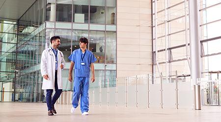Male Medical Staff Talking As They Walk Through Lobby Of Modern Hospital Building