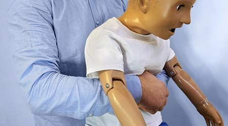 Abdominal thrusts (the Heimlich maneuver or Heimlich manoeuvre) on a simulation mannequin child dummy during medical training Basic Life Support