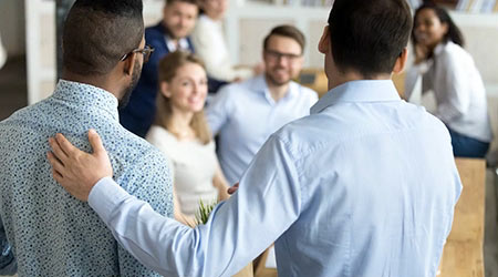 employee having first working day in company standing in front of colleagues, executive manager employer introducing welcoming newcomer to workmates. Human resources employment concept