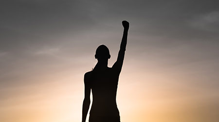 Strong, victorious , and motivated young woman raising her fist up to the sunset sky. Determination and overcoming adversity concept.