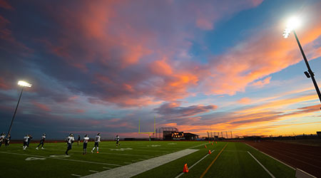 high school football at sunset