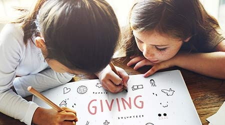 """giving back. two young kids drawing around the word """"giving."""""""