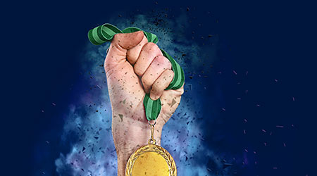Winner raising hand with gold medal surrounded by fume and shatters on blue background, closeup