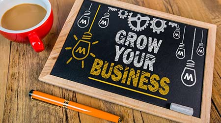"""""""Grow Yours Business"""" written on a small chalkboard"""