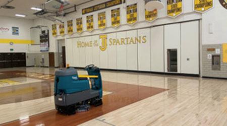 Robotic floor cleaning machine in gymnasium of school
