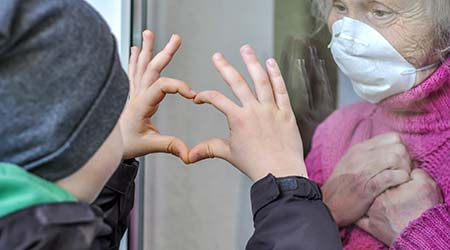 mature woman in a respiratory mask communicates with her grandchild through a window. Elderly quarantined, isolated. Coronavirus covid-19. Caring with older people. Family values, love