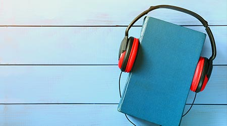 top view of audio book concept, blue book cover and headphones over wooden table  T