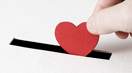 Red heart symbol is put by person's hand into slot of white donation box. Donation concept. life saving or charity. Close-up shot