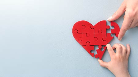 The concept of charity, love, donate and helping hand. International cardiology day. A woman and child arranges red heart-shape puzzle. Symbol of helping others.