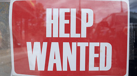 """A red and white """"Help Wanted"""" sign."""