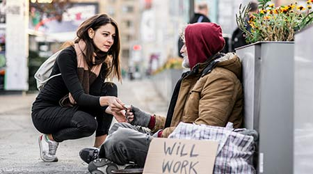 Young woman giving money to homeless  man sitting in city. Man has sign saying he will work for food.