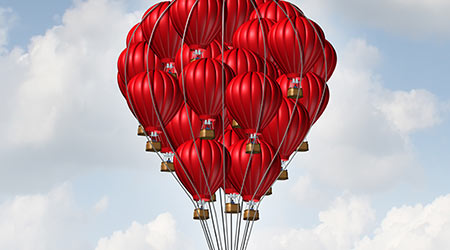 Group concept as a team of red hot air balloons joined together as a symbol for teamwork unity and collaboration solidarity with people being lead by an individual manager.