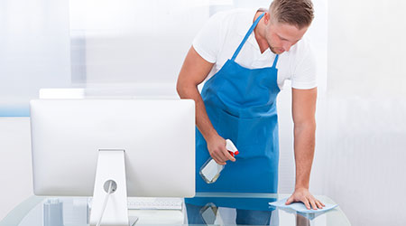 Handsome young janitor or cleaner cleaning an office spraying the top of the desk with disinfectant before the office workers start their day
