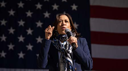 Kamala harris speaks at a political rally in front of American flag