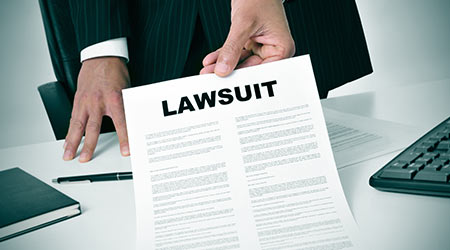 a lawyer in his office showing a document with the text lawsuit written in it