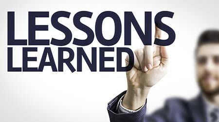 """man pointing at a transparent board that reads """"Lessons Learned"""""""